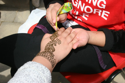 Members of the public have hena patterns drawn on their hands
