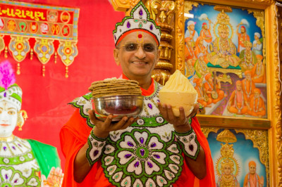 Divine darshan of His Divine Holiness Acharya Swamishree holding freshly churned butter and delicious rotla