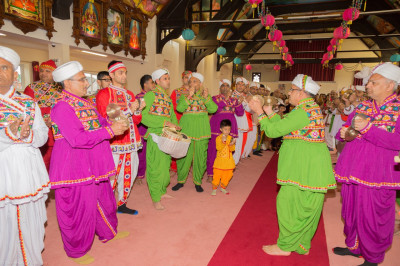 Disciples dressed in vibrant coloured village outfits play traditional instruments and sing devotional songs as His Divine Holiness Acharya Swamishree is escorted to the stage