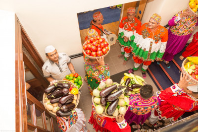 Disciples carry various delicious vegetables into the festival hall