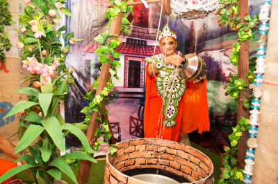 His Divine Holiness Acharaya Swamishree draws water from a well as part of the village scene