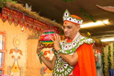 His Divine Holiness Acharya Swamishree carries the raw material for churning butter