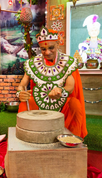 His Divine Holiness Acharya Swamishree uses a traditional hand driven stone grinder to crush fresh millet