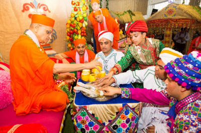 Disciples bathe the divine lotus feet of Lord Shree Swaminarayan with the five nectars
