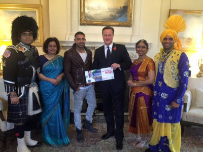 The official invite is presented to Prime Minister David Cameron at 10 Downing Street