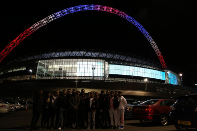Performers of Shree Muktajeevan Swamibapa Pipe Band Bolton and Dhol academy members in front of Wembley Stadium lit up in the UK's red white and blue