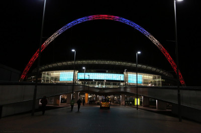 The Wembley Stadium arch is lit with the colours from the UK national flag