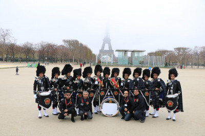 Shree Muktajeevan Swamibapa Pipe Band Bolton in front of the Eiffel Tower on a misty morning