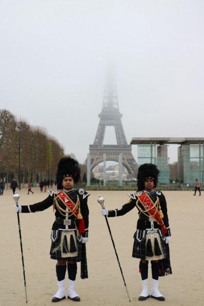 The drum majors of Shree Muktajeevan Swamibapa Pipe Band Bolton in front of the Eiffel Tower