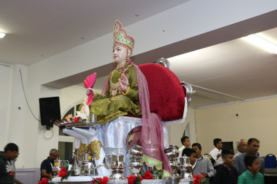 Divine darshan of Lord Shree Swaminarayan seated at the centre of the hall