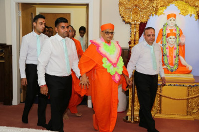Disciples who have sponsored the event escort His Divine Holiness Acharya Swamishree into the mandir