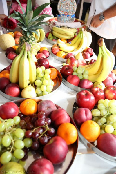 An array of carefully arranged fruits are prepared for young disciples to carry and offer the Lord