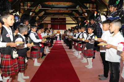 Shree Muktajeevan Swamibapa Pipe Band Bolton perform as disciples carry gifts for the Lord in the mandir hall