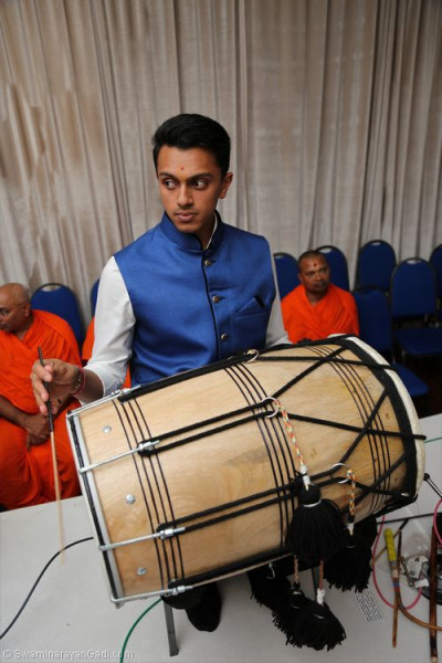 Disciples perform dhol to accompany devotional song performances