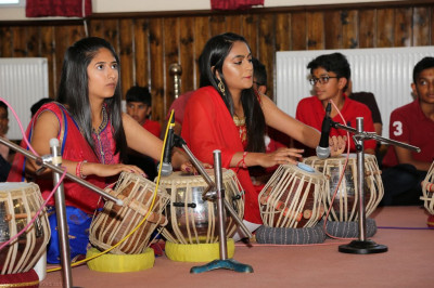 Young disciples perform tabla pieces to please the Lord
