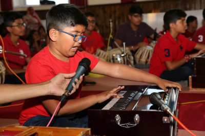 Young disciples perform on the harmonium