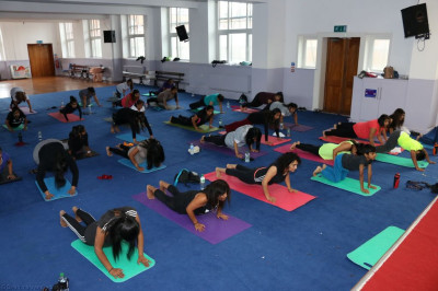 Disciples and members of the local commuunity perform yoga together