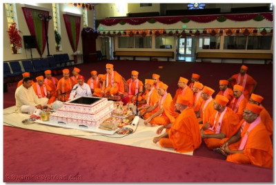 Acharya Swamishree performs the yagna ceremony with sants seated beside Him