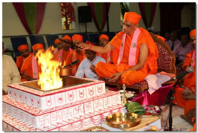 Acharya Swamishree pours ghee into the yagna fire