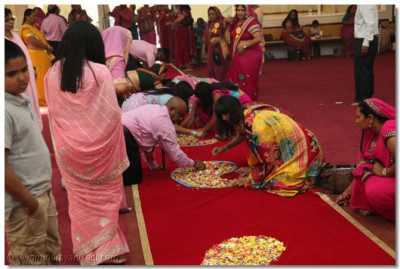 Disciples decorate the center carpet with flower petals for Acharya Swamishree to place His divine lotus feet on when He enters the temple after performing the ribbon-cutting ceremony