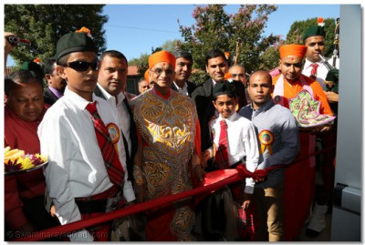 Acharya Swamishree performs the ribbon-cutting ceremony