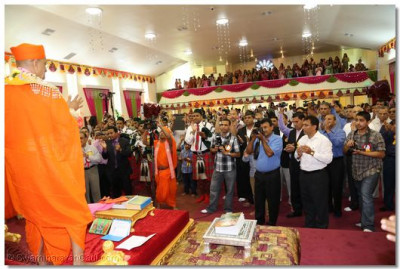 The entire congregation sings, claps, and dances along with Acharya Swamishree