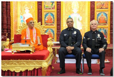 The LAPD Van Nuys area captains sit beside Acharya Swamishree