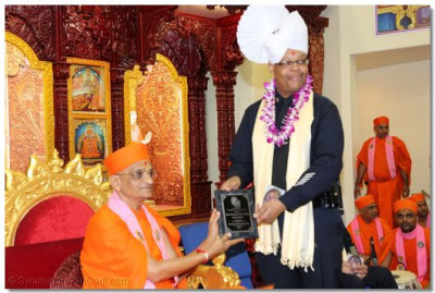 Captain and Chief Officer Paul Snell presents Acharya Swamishree with an honorary plaque for the temple's generous support of  the Police Department