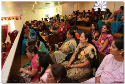Disciples sit in the balcony of the temple prayer hall to listen to Acharya Swamishree's ashirwad