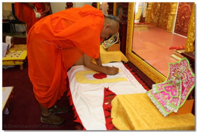 Acharya Swamishree sanctifies and signs the dhaja (flag) for the Los Angeles Temple flag-raising ceremony