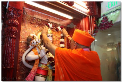 Acharya Swamishree adorns Shree Hanumanji with a flower garland to install His idol in the temple