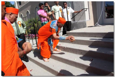 Acharya Swamishree breaks open a coconut for use in the flag-raising ceremony