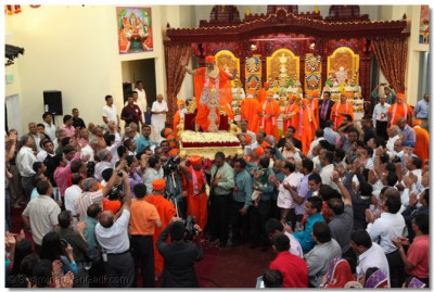 Acharya Swamishree is adorned in beautiful vagha, showered with thousands of flower petals, and carried around on His gadi in honor of His 70th manifestation day anniversary