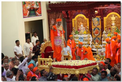 Divine darshan of Acharya Swamishree standing atop His gadi as the entire sabha exuberantly crowds the area