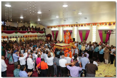 Sants and disciples swarm Acharya Swamishree's gadi and carry it throughout the temple prayer hall