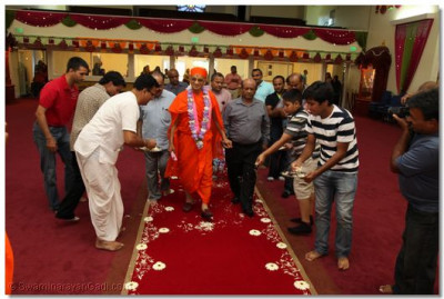 Disciples Welcome His Divine Holiness Acharya Swamishree by offering flowers at his lotus feet
