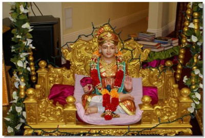 Lord Shree Swaminarayan seated in a Golden ornate swing