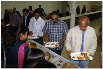 Devotees enjoying prasad at the conclusion of the event
