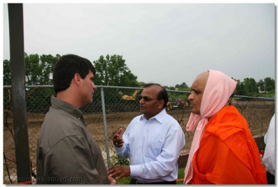 Acharya Swamishree and a disciple speak to the temple's engineer