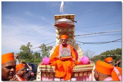 Acharya Swamishree is seated on a grand chariot