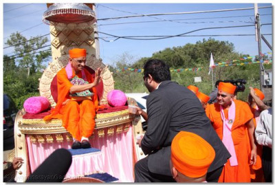 Acharya Swamishree blesses a member of the escort team