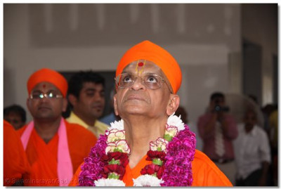 Acharya Swamishree observes the temple�s progress as he walks into the temple