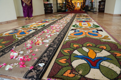Disciples prepared an intricate rangoli design, using various grains and nuts, to welcome Acharya Swamishree and sants