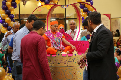 Acharya Swamishree is welcomed by disciples in a grand indoor float