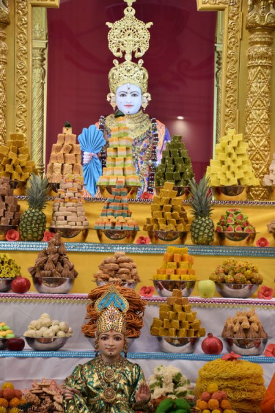 Divine darshan of Lord Shree Swaminarayan dining on the annakut of sweet and savoury items