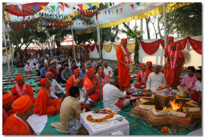 Acharya Swamishree performs aarti during the Yagna ceremony