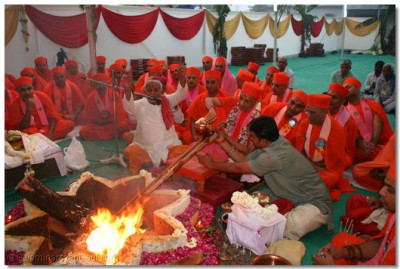 Acharya Swamishree offers ghee into the ceremonial fire