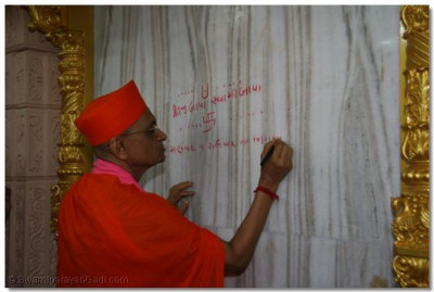 Acharya Swamishree scribes the divine name of Lord Swaminarayan before installing the new murti