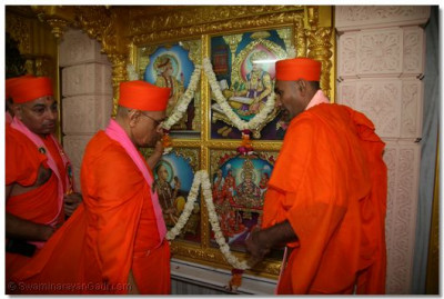 Acharya Swamishree installs the new murtis inside the temple
