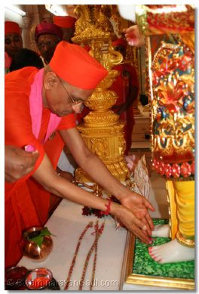 As part of the installation ceremony, Acharya Swamishree presents fragrant roses to the divine feet of Lord Swaminarayan